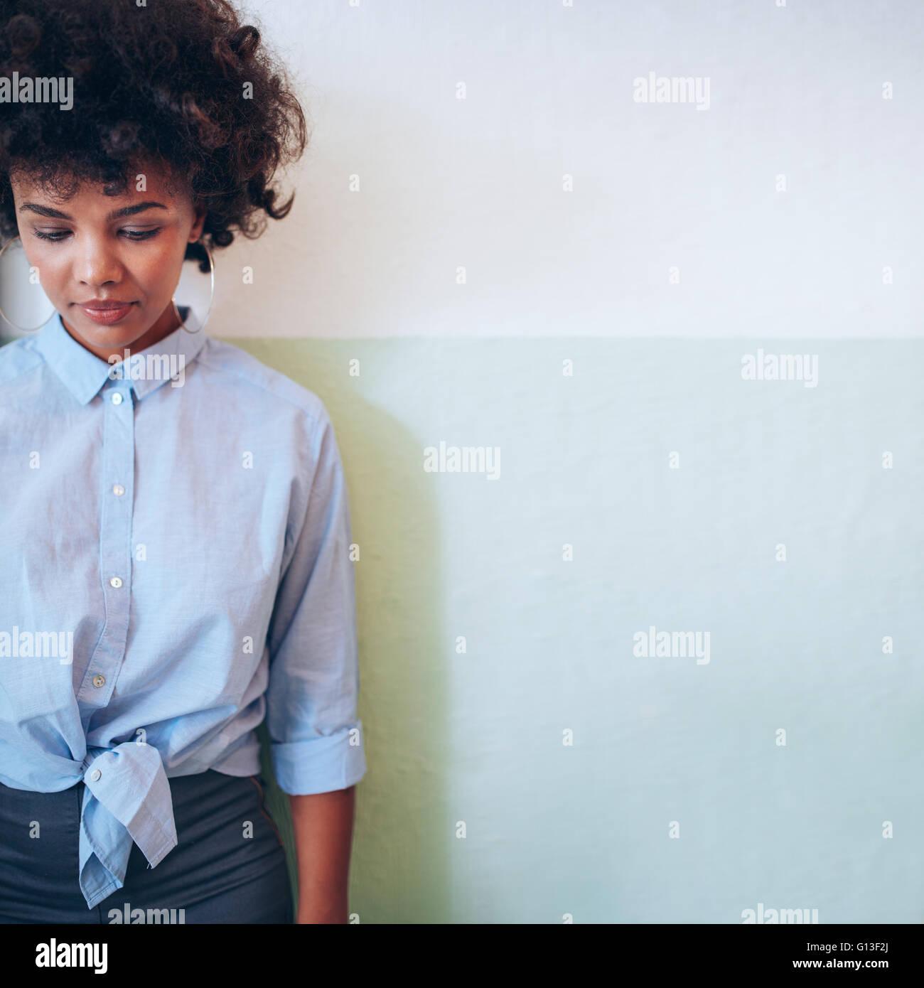 Imagen recortada de la hermosa joven africana de pie contra la pared y mirando hacia abajo. Hembra de raza mixta Imagen De Stock