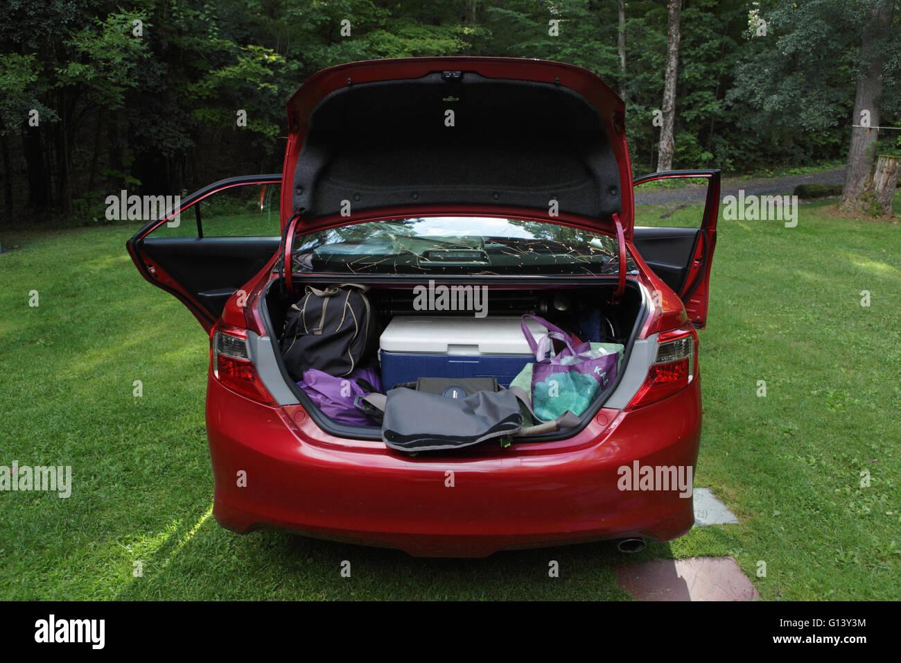 Tronco y coche puertas abiertas mostrando lo que una familia comidas para un viaje de vacaciones a una cabaña Imagen De Stock