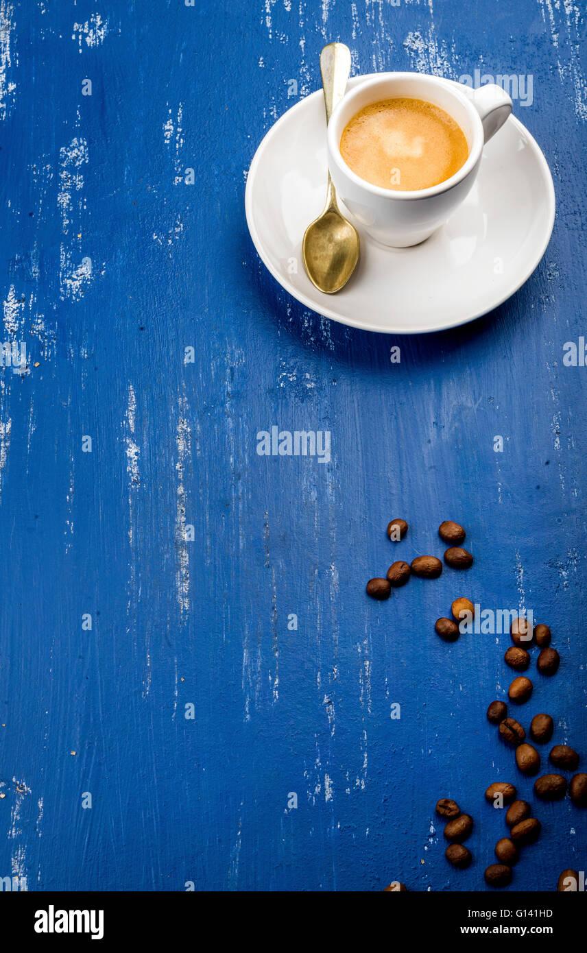 Taza de café espresso y frijoles en madera pintada de azul de fondo de la tabla. Vista superior, vertical Imagen De Stock