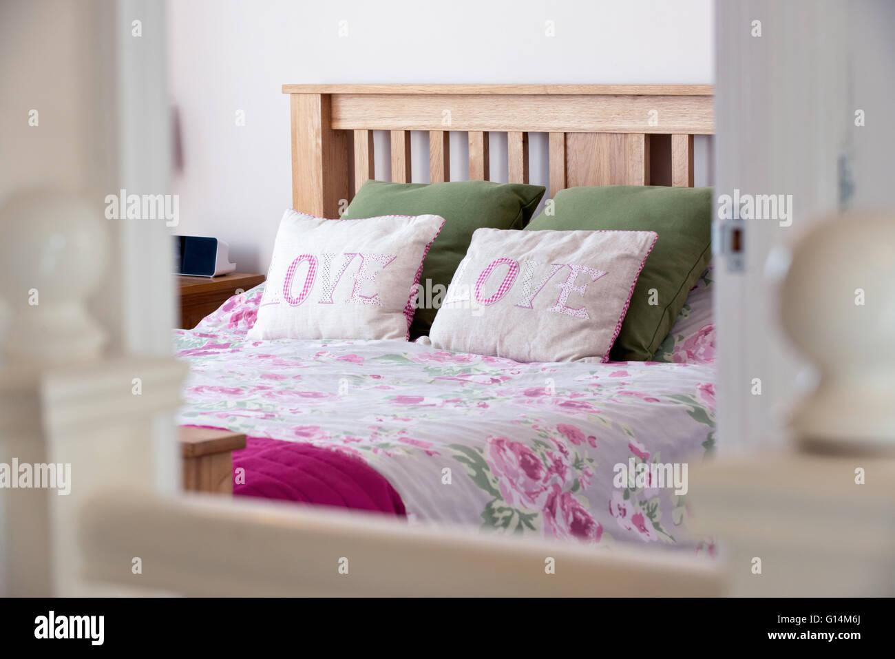 Una imagen de estilo de vida de una cama vestida en una casa de familia, con almohadas blasonadas con la palabra Foto de stock