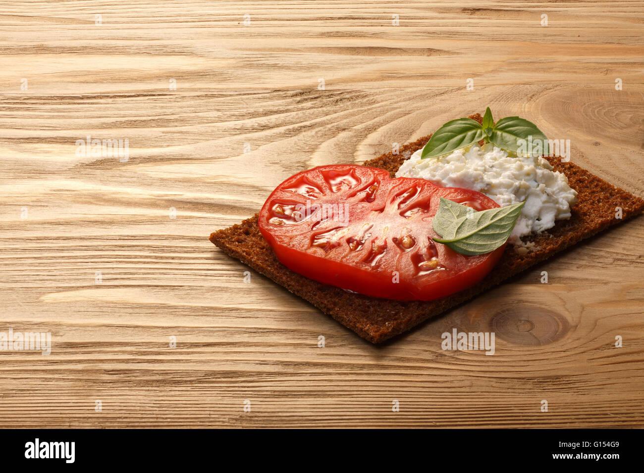 Pan crujiente pan tostado escandinavo (sandwich) con frontal abierto con herencia de tomate, crema de queso y hojas de albahaca fresca sobre la mesa de madera. Infinito Foto de stock