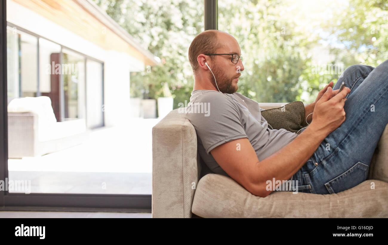 Vista lateral de la imagen de un hombre con su tablet mientras está sentado en el sofá en casa. Hombre Imagen De Stock