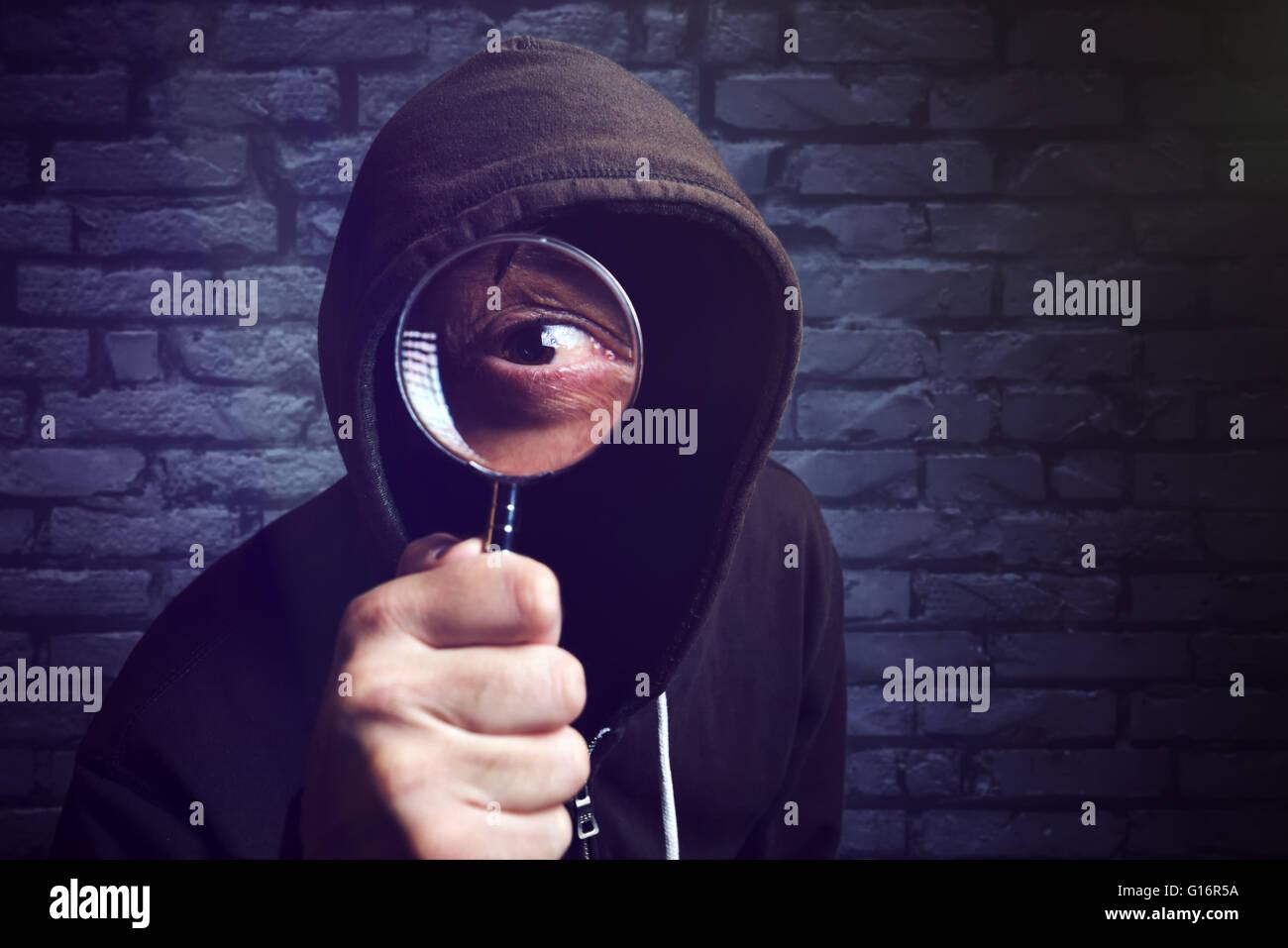 Hacker encapuchados con lupa, hacker internet seguridad online y concepto. Imagen De Stock
