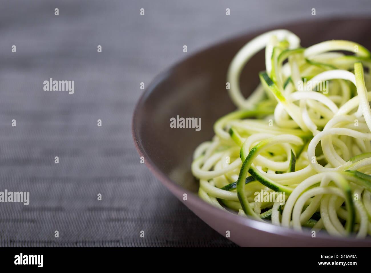 Un tazón de calabacín (zucchini) fideos (espaguetis) realizados mediante un spiralizer Imagen De Stock