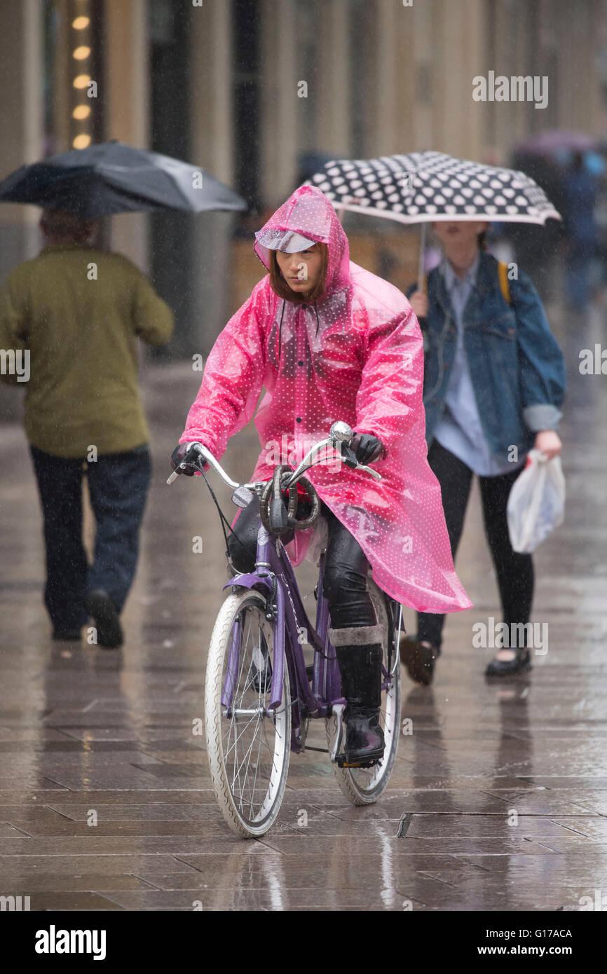 Una mujer asiática viste un poncho rosa mientras viajaba en una moto  durante el clima húmedo c235729c7ba