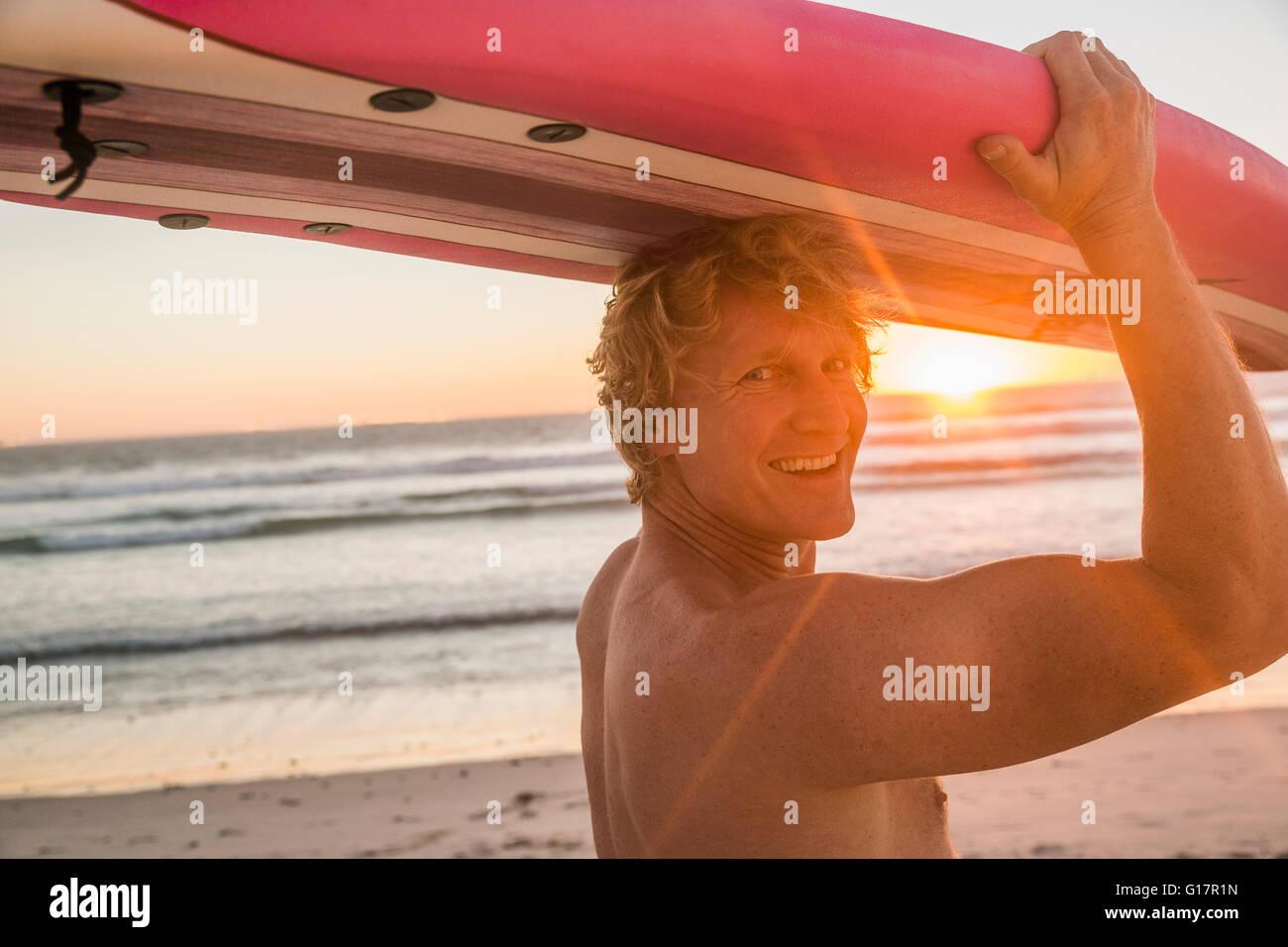 Hombre en playa Surf llevando sobre la cabeza mirando por encima del hombro a la cámara sonriendo Foto de stock