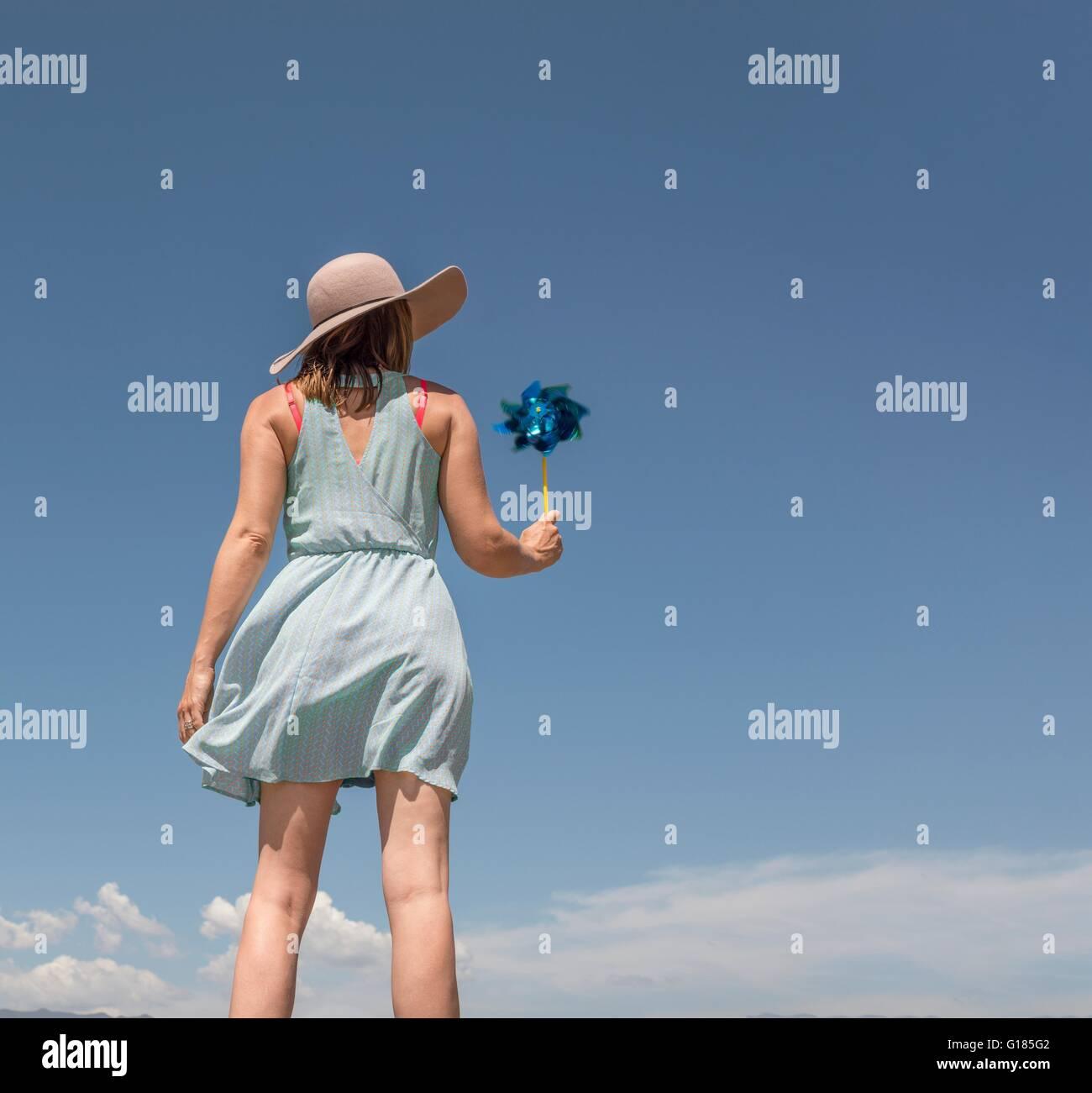 Vista trasera de una mujer con sombrero la celebración de molinos de papel Foto de stock