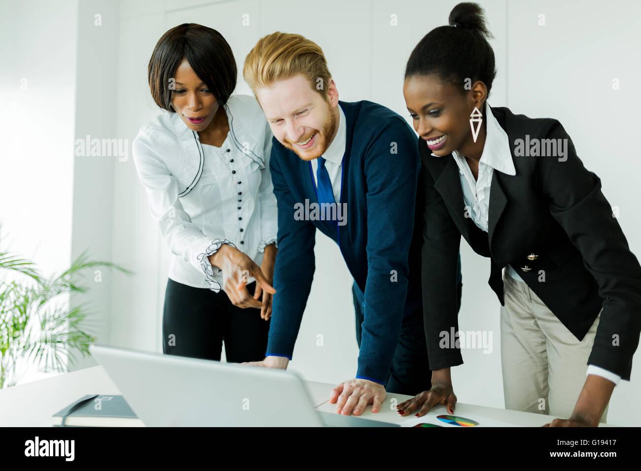 Lluvia de ideas de negocios por feliz, bien vestida pueblo multiétnico en un lugar limpio, blanco office Foto de stock