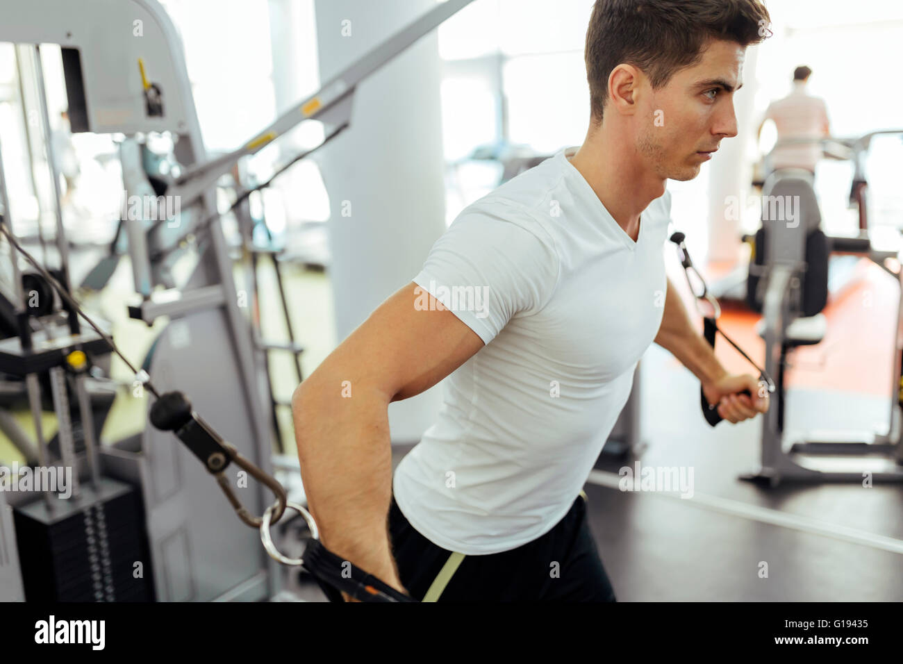 Guapo entrenamiento en el gimnasio moderno y limpio en las diferentes máquinas Imagen De Stock