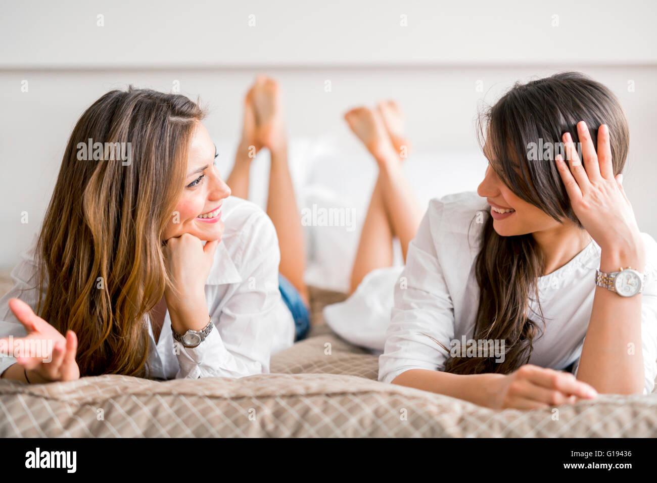 Dos hermosas chicas hablando y sonriendo mientras está acostado en una cama de lujo Imagen De Stock