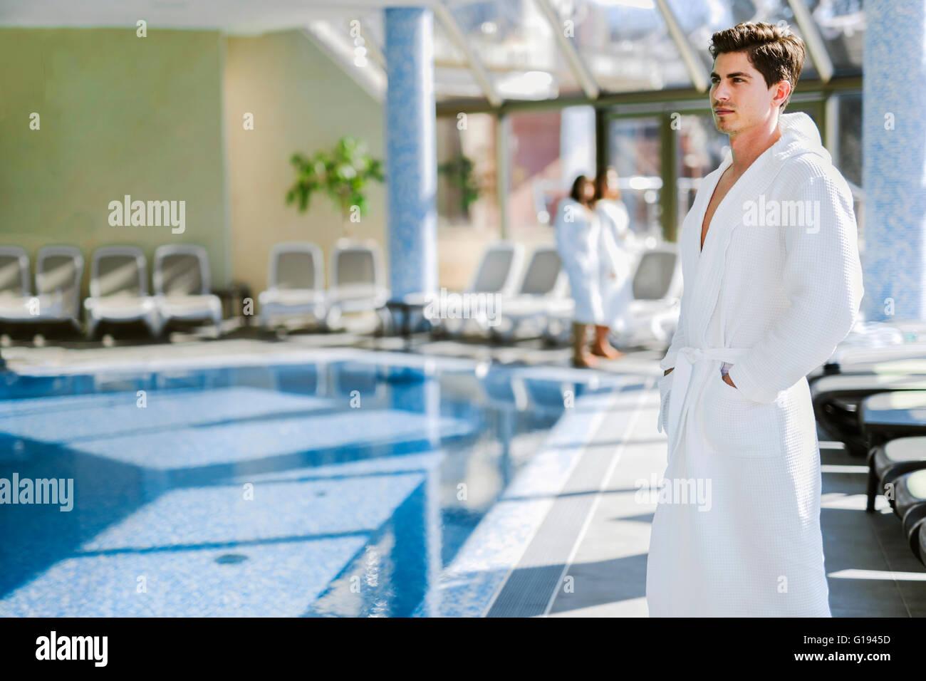 Hombre de pie junto a una piscina en un manto y relajante Imagen De Stock