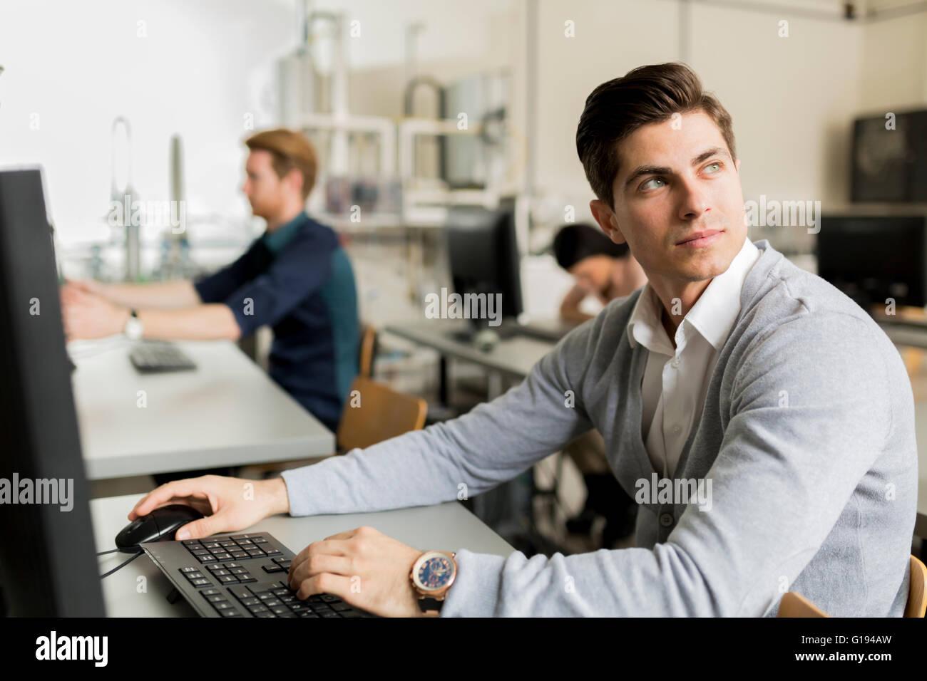 Joven apuesto estudiante utilizando el ordenador en el aula Imagen De Stock
