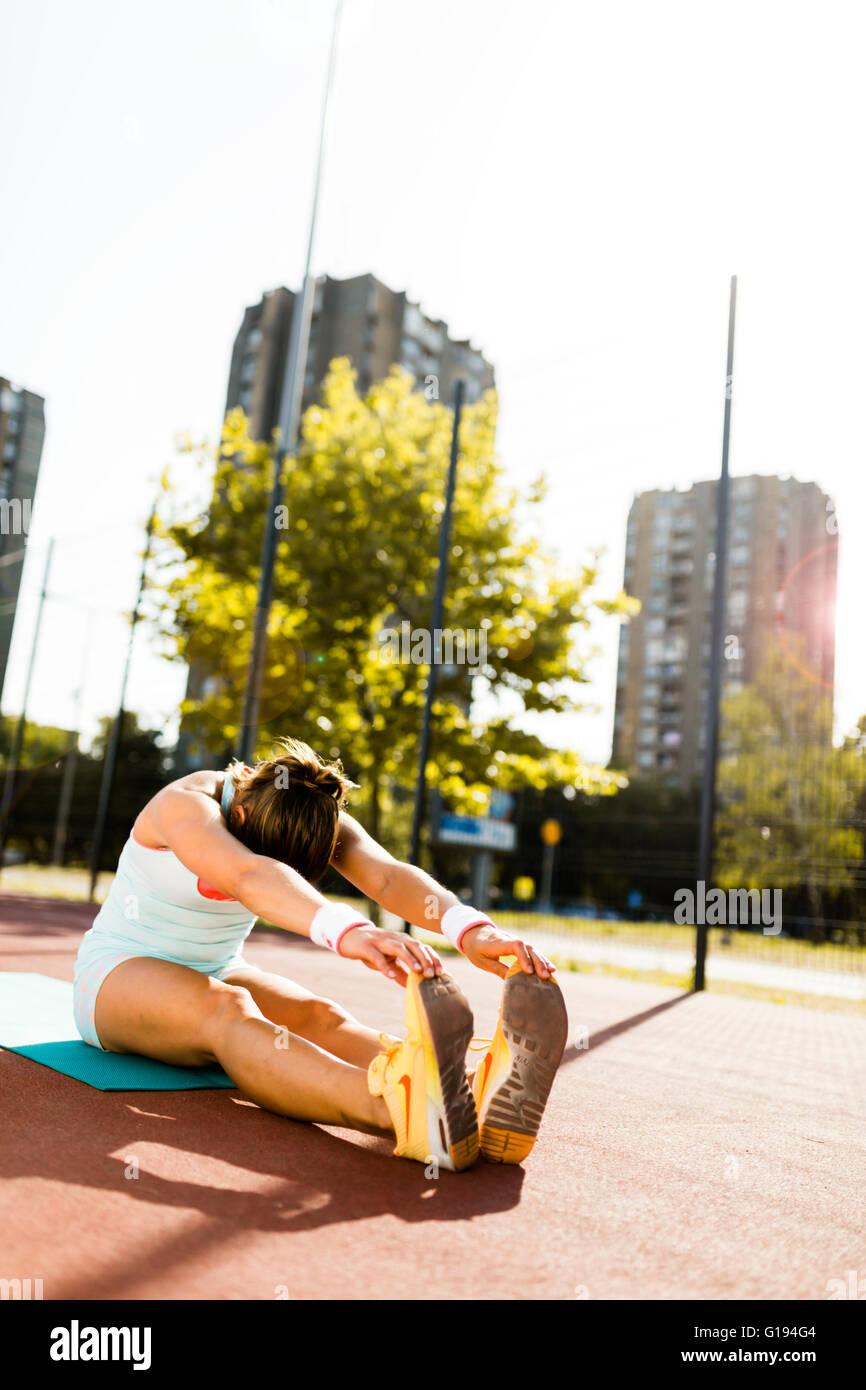 Joven y bella mujer atlética estiramiento en verano antes de ejecutar Imagen De Stock