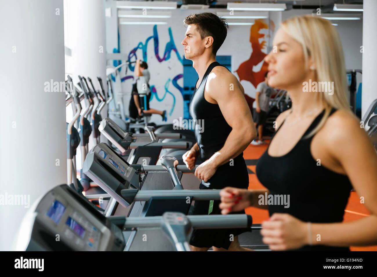 La gente corriendo en cintas de correr en el gimnasio para mantener el cuerpo en forma Imagen De Stock