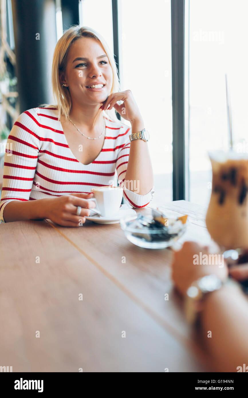 Hermosas Mujeres bebiendo café y chismes en bonito restaurante Imagen De Stock