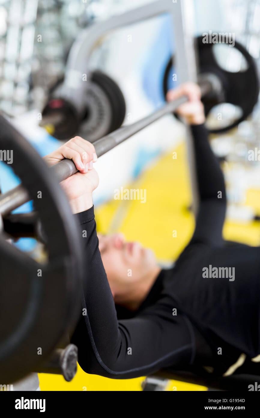 Primer plano de una joven apuesto macho haciendo ejercicios sobre un banco de prensa Imagen De Stock