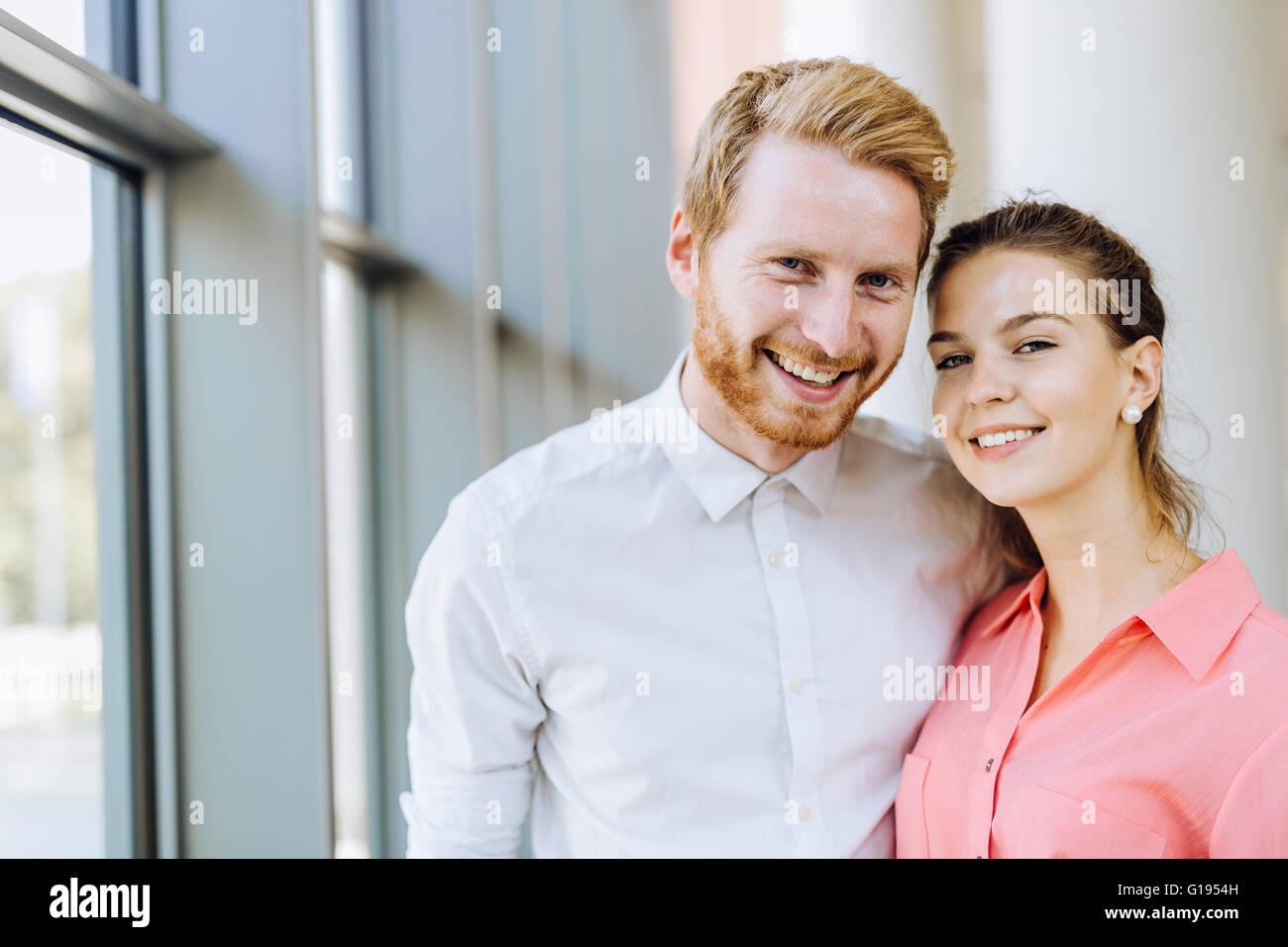 Hermosa colegas de negocios sonriendo y estar cerca unos de otros. Sinceros sentimientos Imagen De Stock