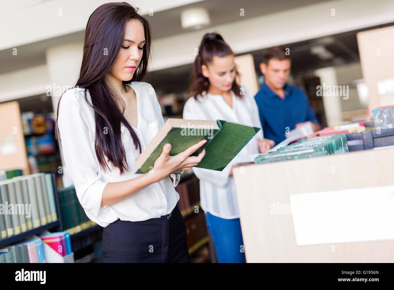 Los estudiantes inteligentes leyendo y estudiando en la búsqueda a través de toda la biblioteca de libros Imagen De Stock