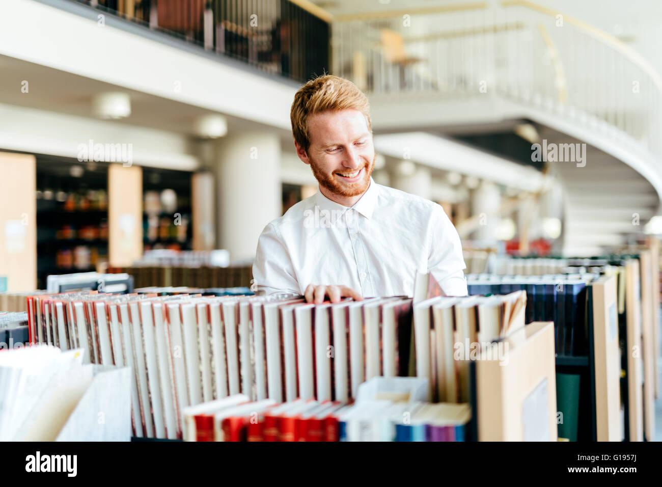 Guapo estudiante buscando un libro en una bonita librería Imagen De Stock