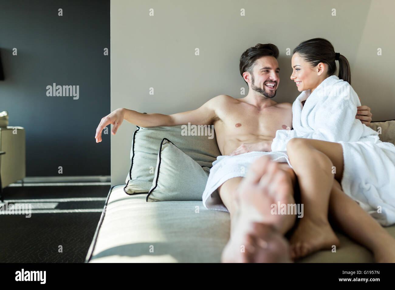 Pareja encantadora relajante en un centro de bienestar, sentando en una toalla y rob Imagen De Stock