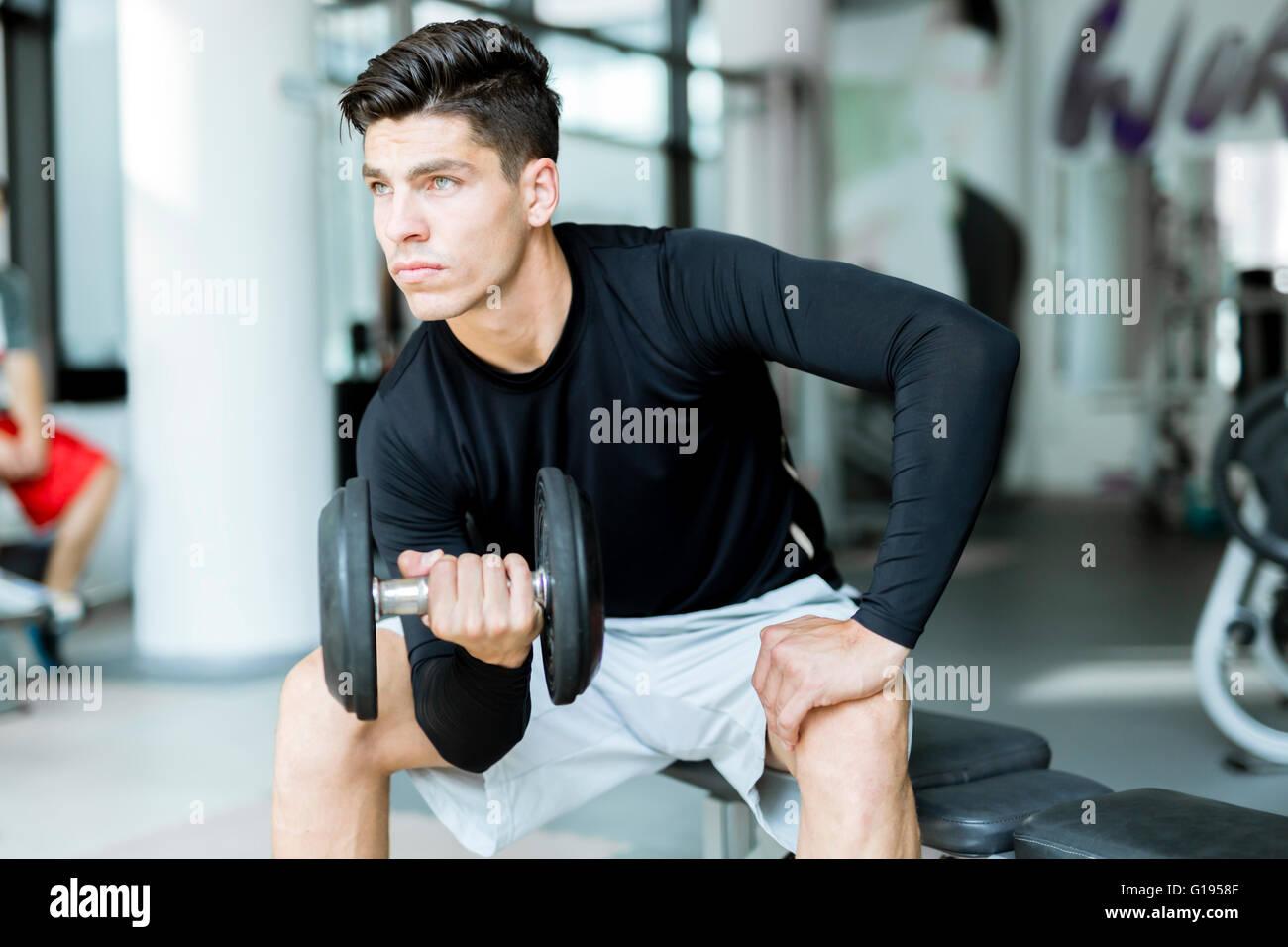 Joven apuesto hombre la formación en un centro de fitness Imagen De Stock
