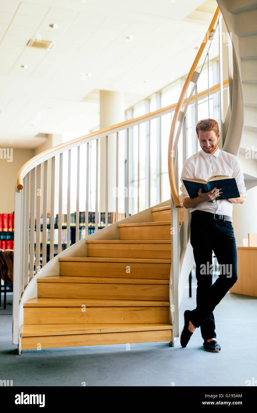 Apuesto hombre inteligente y leer un libro en una biblioteca Imagen De Stock