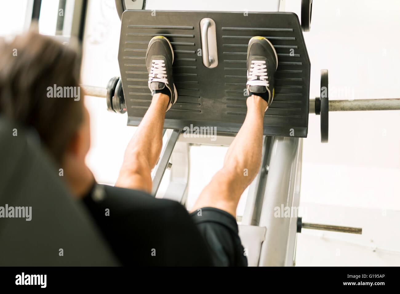 Macho joven trabajando en el gimnasio y haciendo ejercicios para las piernas Imagen De Stock