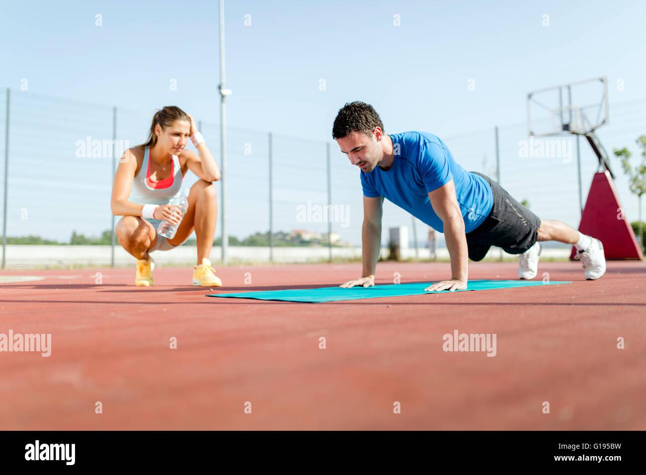 Jóvenes, bellos, sanos y entrenador personal contando push-ups y motivar Foto de stock