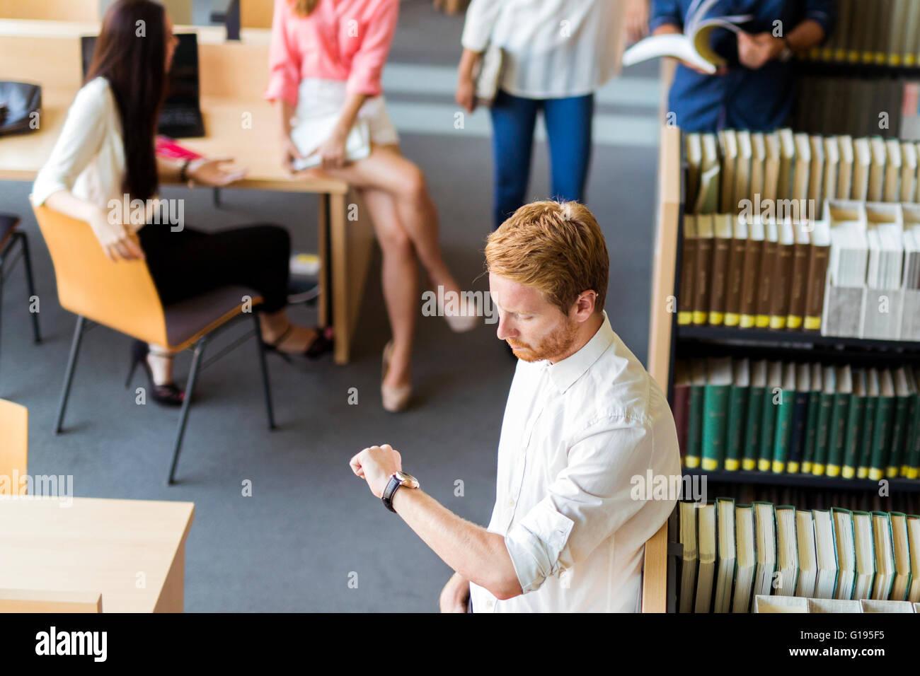 Grupo de jóvenes que se preparan para un exame en una biblioteca y no queda mucho tiempo. Fecha límite Foto de stock