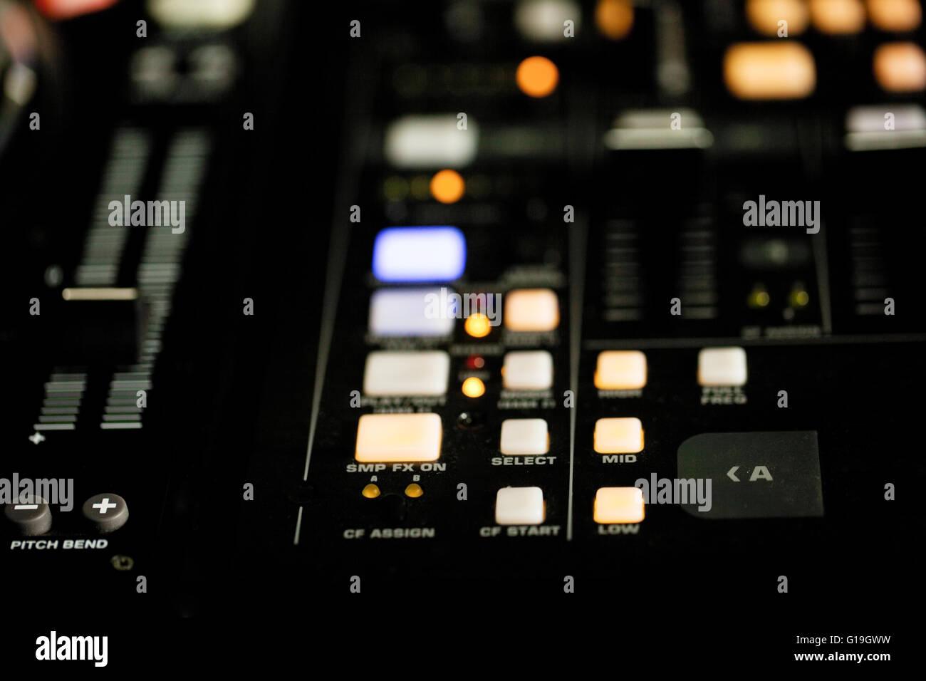 Acercamiento de las luces iluminadas en la cubierta de un DJ en la noche durante una actuación en un club nocturno o discoteca Foto de stock
