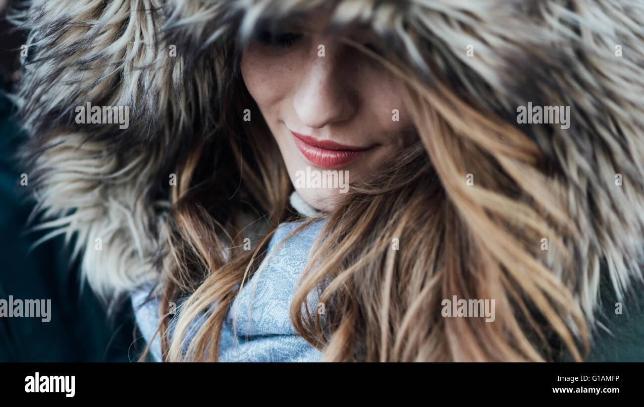 Mujer sonriente joven con capucha de pieles, la moda y el concepto de invierno Imagen De Stock