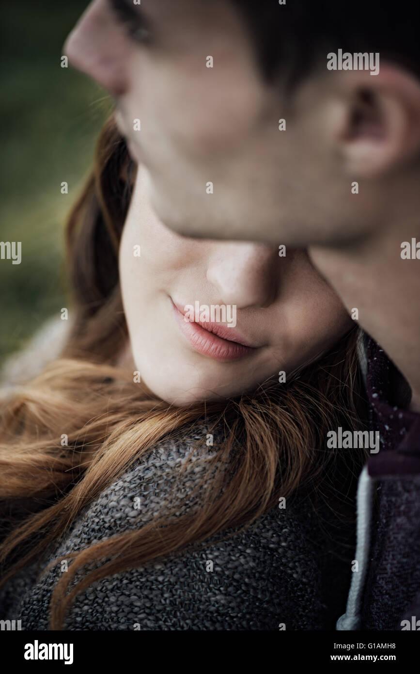 Joven pareja amorosa relajante sobre el césped y abrazos, ella está sonriendo y apoyada sobre su hombro, Imagen De Stock