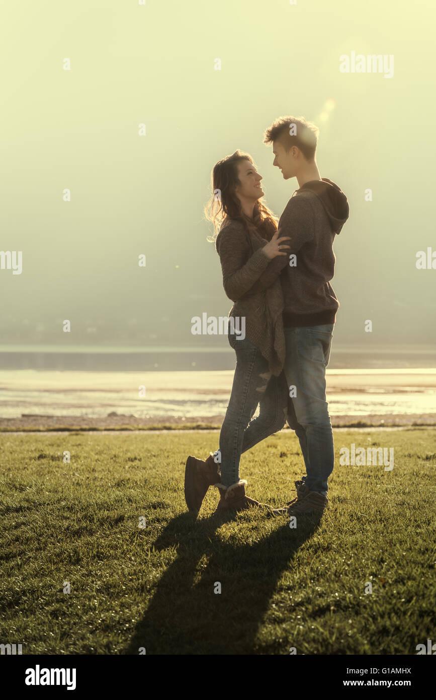 Feliz pareja enamorada romántica en el lago abrazando y mirando fijamente el uno al otro, el amor y las relaciones Imagen De Stock