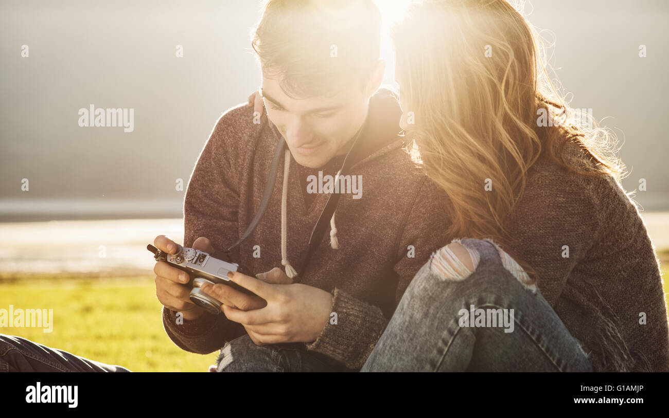 Pareja joven sentado en la hierba en la luz del sol y viendo las imágenes de una cámara digital, la amistad Imagen De Stock