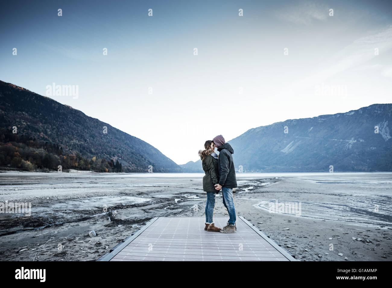 Joven pareja romántica en un muelle cogidos de la mano, el lago y las montañas al fondo Foto de stock