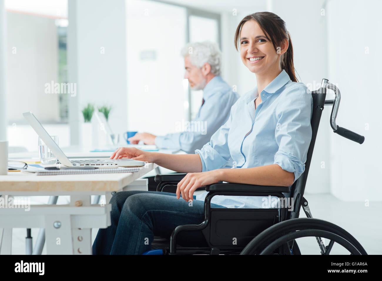 Seguro feliz empresaria en silla de ruedas trabajan en la oficina y utilizando un ordenador portátil, ella está Foto de stock