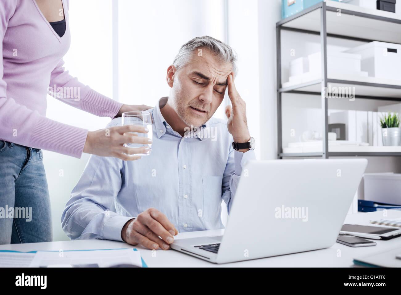 Cansado del empresario en la oficina trabajando en el escritorio y tener un dolor de cabeza fuerte, su colega es Imagen De Stock