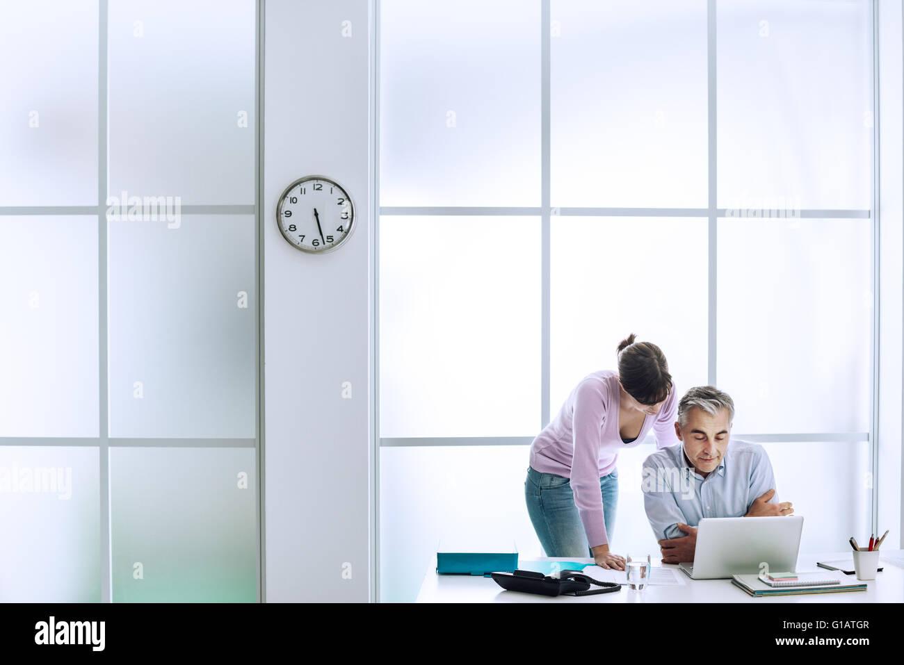 Ejecutivo que trabaja en la oficina con su asistente, están utilizando un ordenador portátil y conexión Imagen De Stock