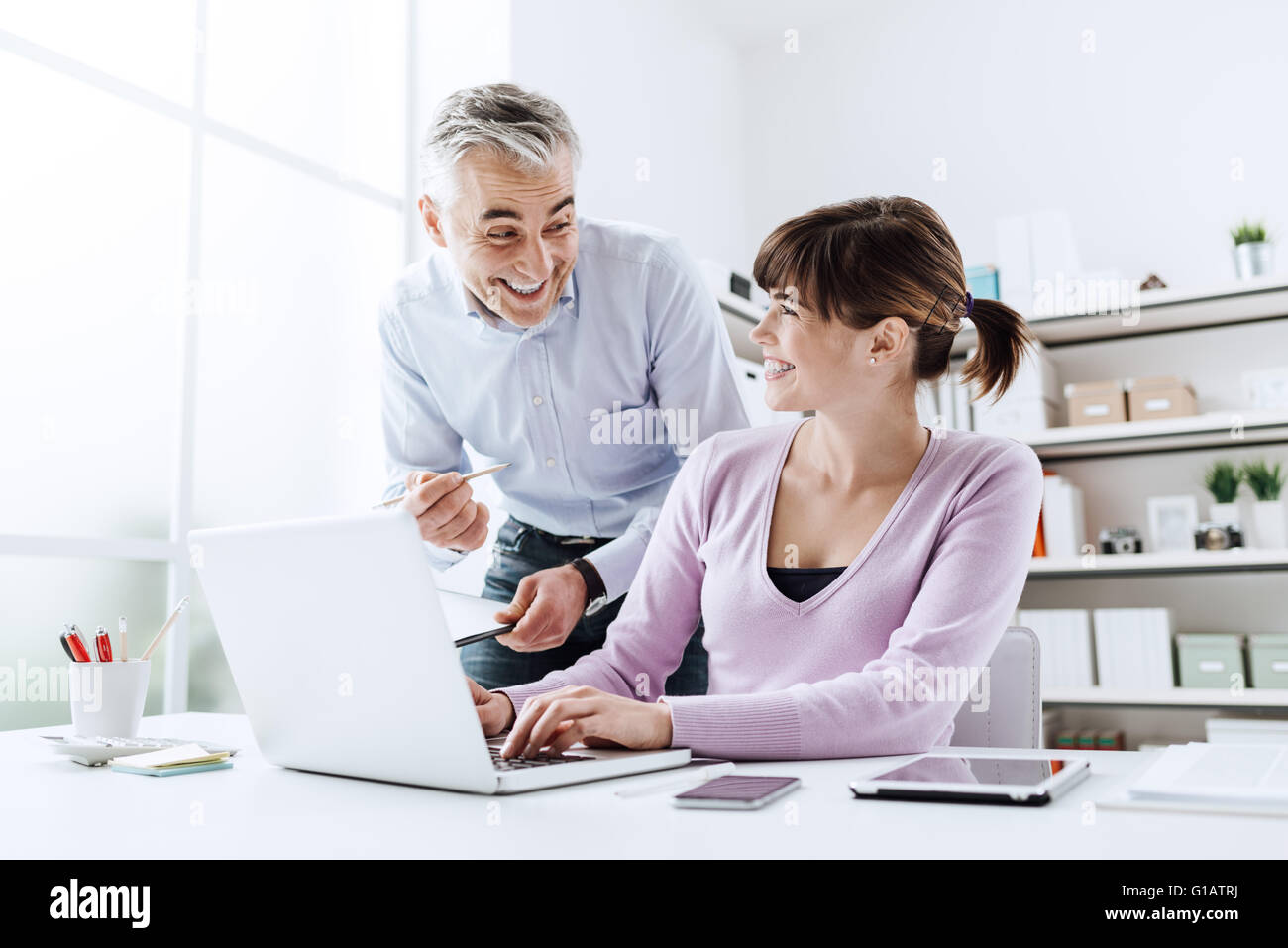 La alegre gente de negocios en la oficina, están trabajando juntos, y sonriendo, la mujer está escribiendo Imagen De Stock
