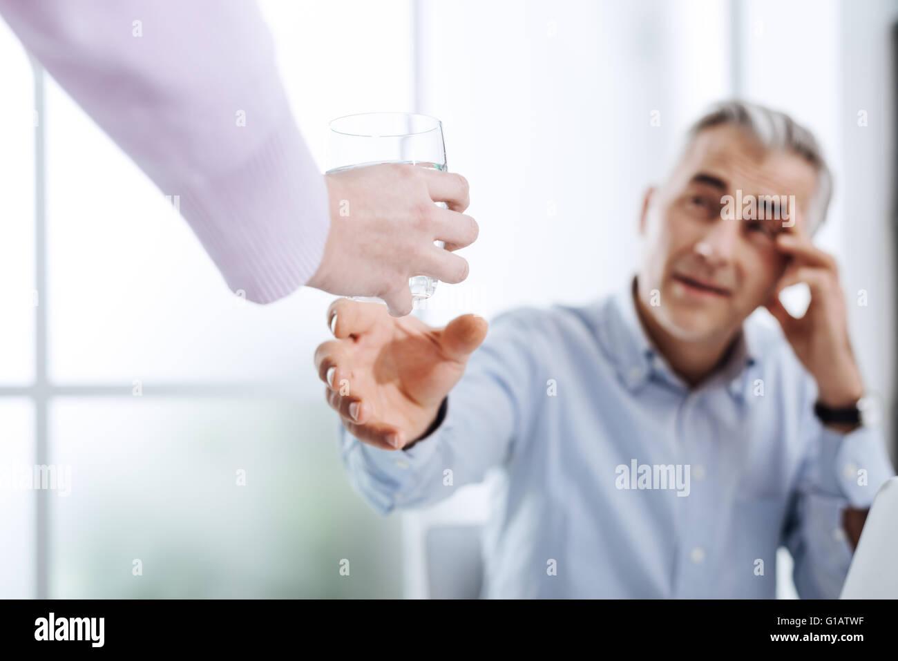 Agotado el empresario trabajando en su oficina y tener un dolor de cabeza, su ayudante, se le entregaba un vaso Imagen De Stock