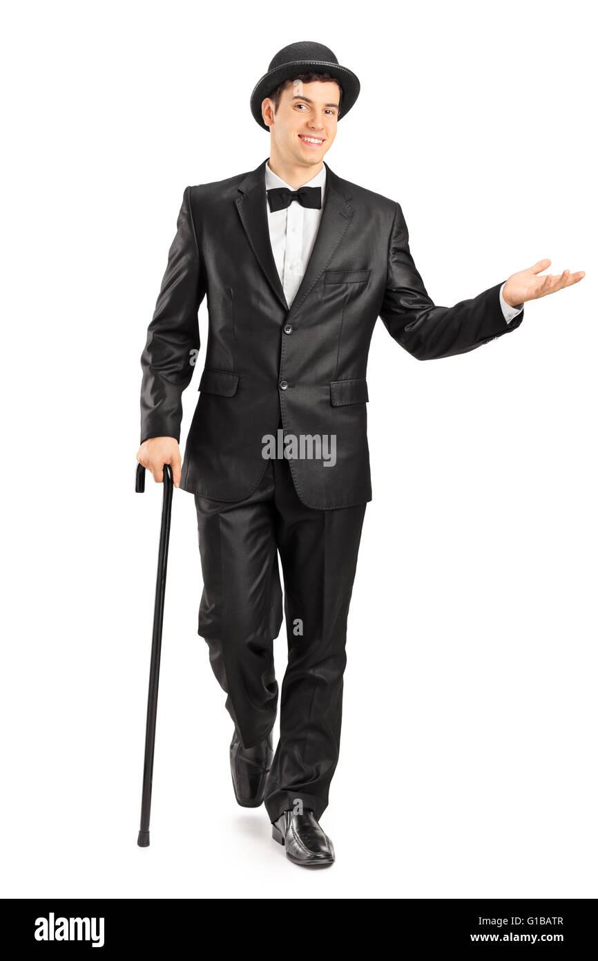 Longitud total retrato de un joven caballero en un elegante traje negro  caminando con bastón aislado sobre fondo blanco. e3c2b9d8954