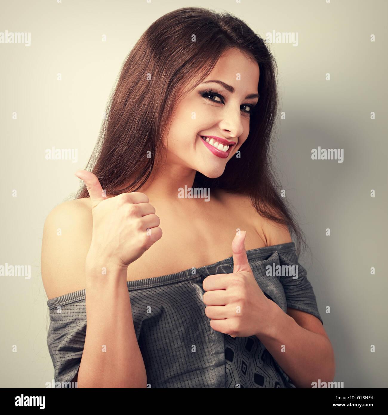 Feliz optimista mujer morena mostrando pulgar arriba firmar. Vintage tonos closeup retrato Imagen De Stock