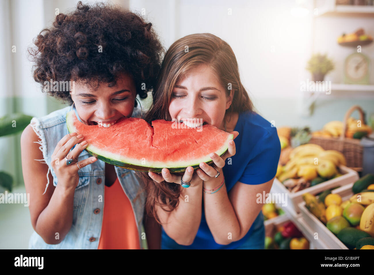 Dos joven Comiendo Sandía y divertirse. Hembra de raza mixta amigos comiendo una rebanada de sandía. Imagen De Stock