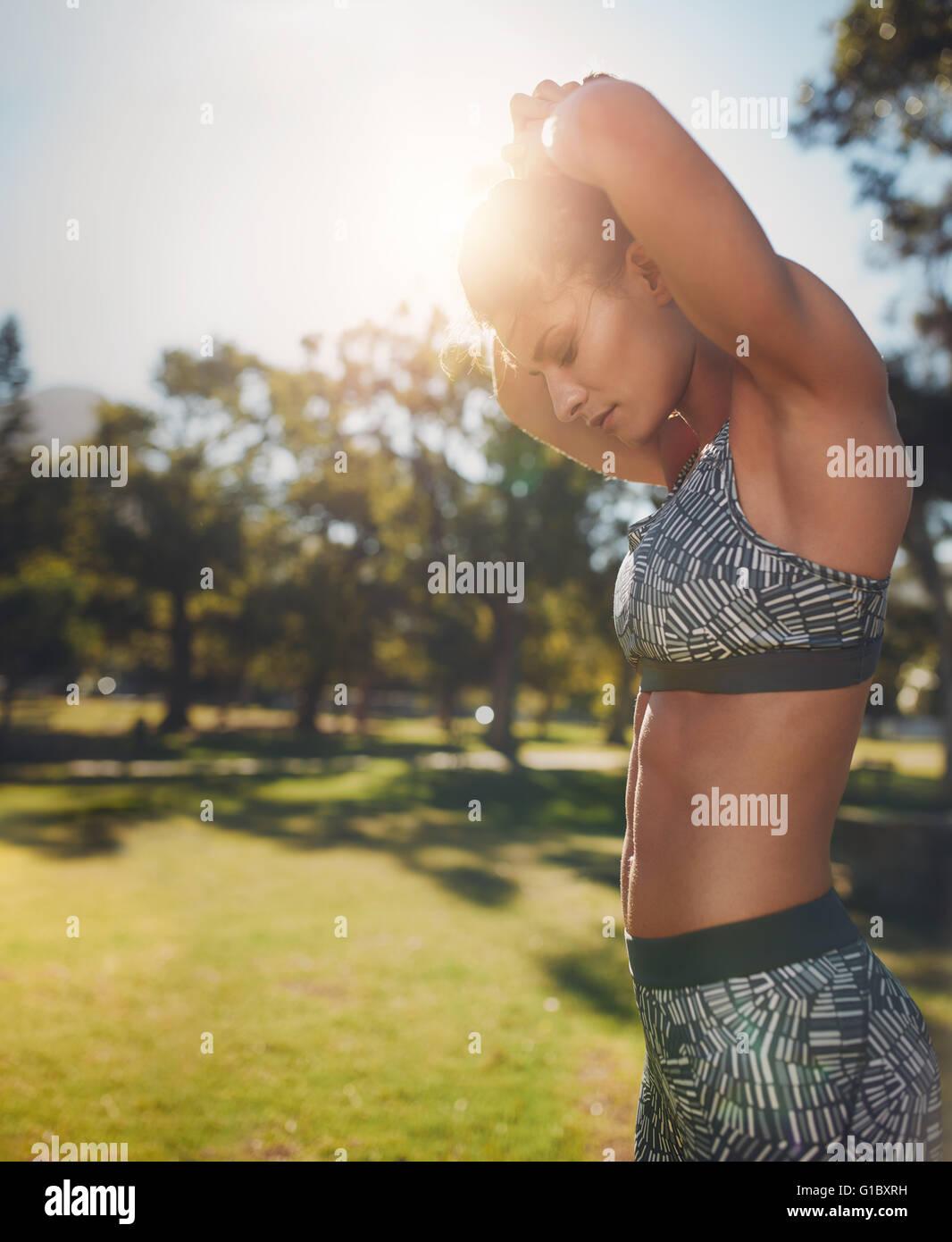 Vista lateral de ajuste de imagen joven algo de ejercicio en el parque. Mujeres Saludables con fuertes seis-embala Imagen De Stock