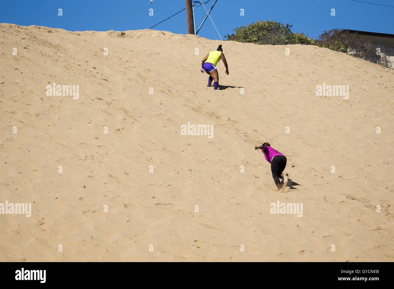 Manhattan Beach, California, EE.UU. - Octubre 10, 2015: Dos mujeres subiendo una duna de arena como parte de un Imagen De Stock