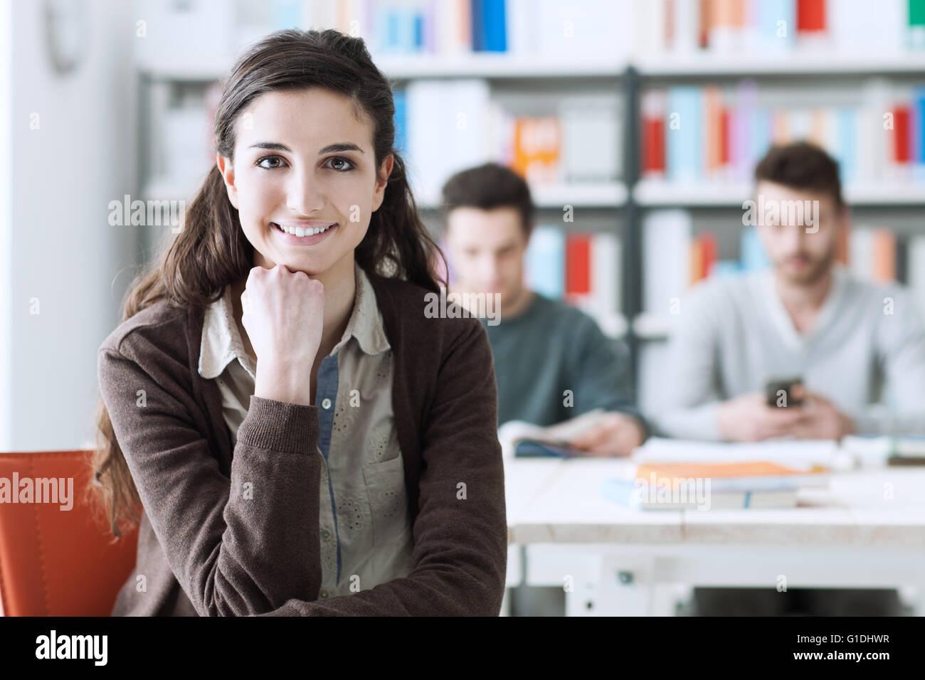 Sonriente joven estudiante en la biblioteca mirando a la cámara, sus compañeros están sentados en Imagen De Stock