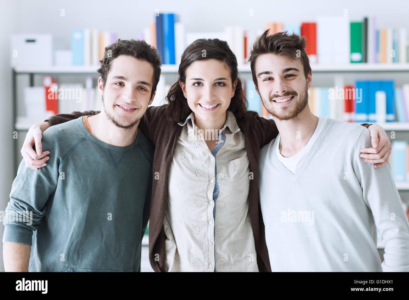 Adolescente en la biblioteca de amigos posando juntos y abrazarse, la juventud y la amistad concepto Imagen De Stock
