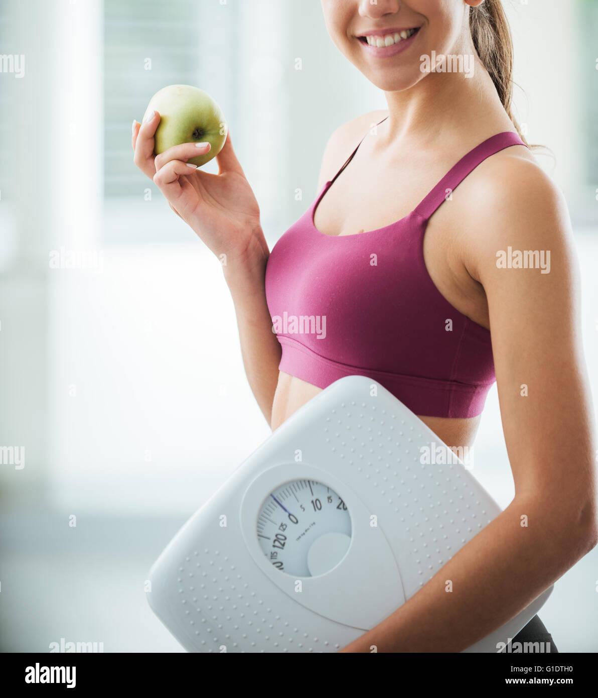 Adolescente sonriente sosteniendo una balanza y una manzana fresca, comer sano, fitness y pérdida de peso concepto Imagen De Stock