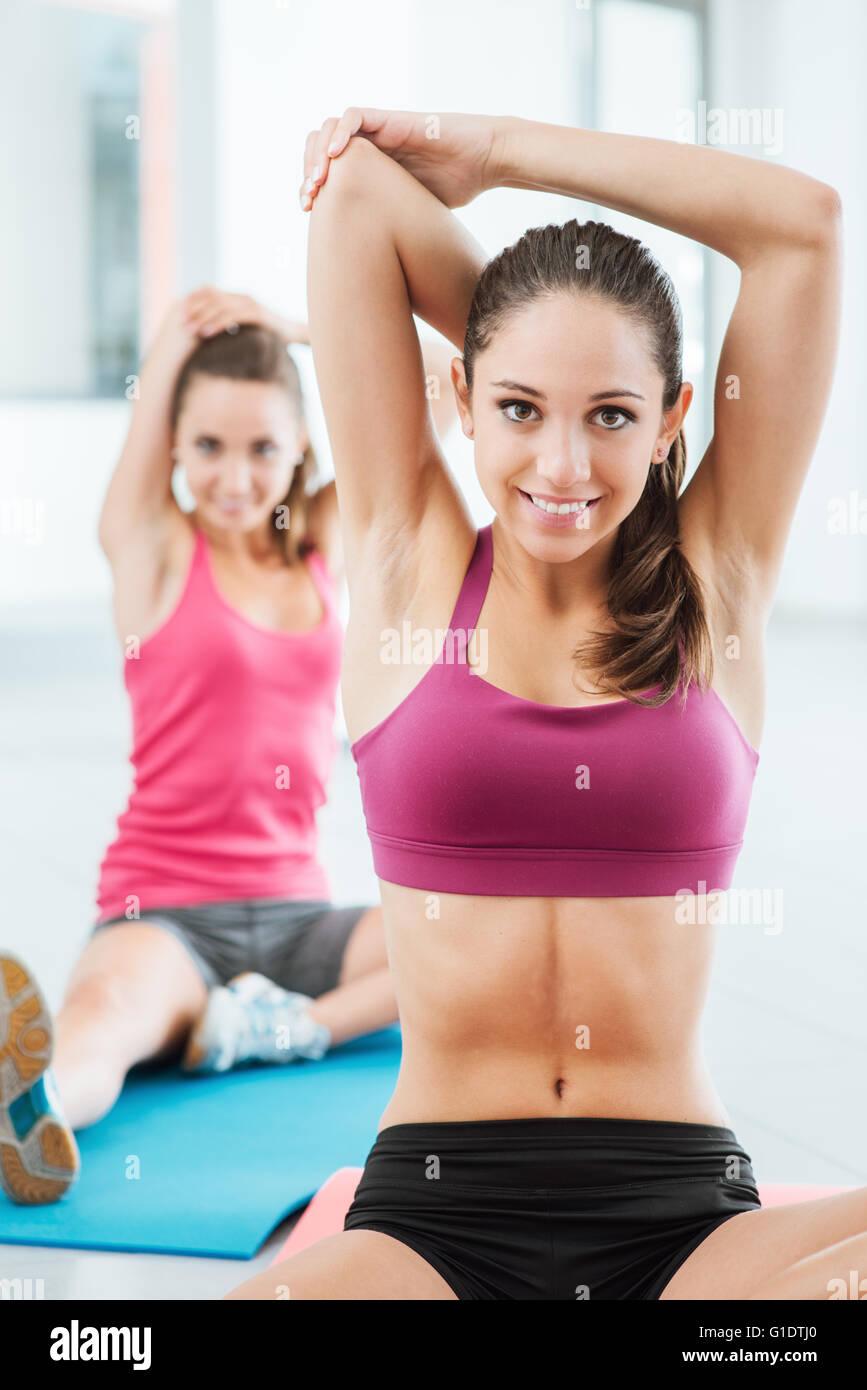 Las mujeres jóvenes en el gimnasio sentado sobre una estera y hacer ejercicios de estiramiento para los brazos Imagen De Stock