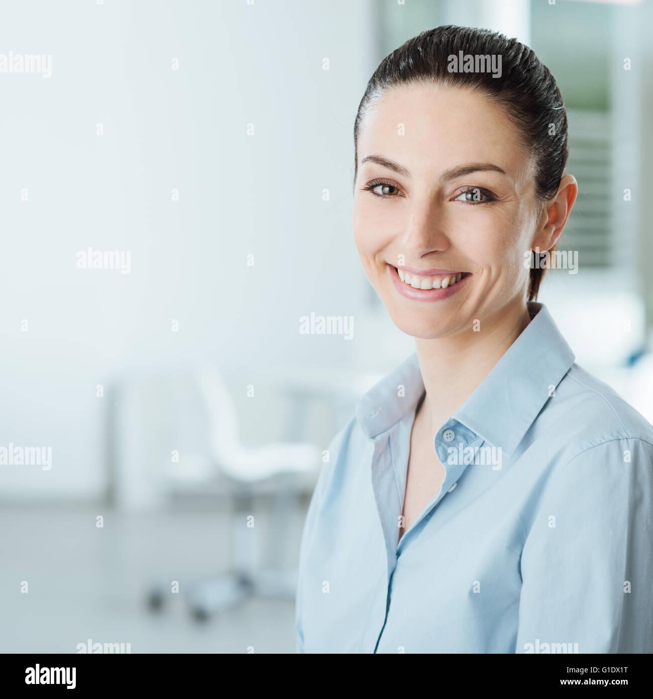 Sonriente joven y bella mujer de negocios sonriendo y mirando a la cámara, en el interior de la oficina del Imagen De Stock